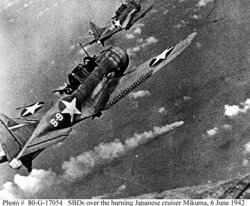 Dive bombers over the burning Japanese cruiser Mikuma during the Battle of Midway